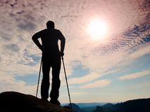 Silhouette of tourist with poles in hand. Hiker stand on rocky view point above misty valley. Sunny daybreak in rocky mountains Royalty Free Stock Photo
