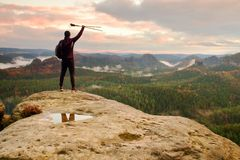 Silhouette of tourist with poles in hand. Sunny spring daybreak in rocky mountains. Hiker with sporty backpack stand on rock Royalty Free Stock Image