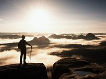 Silhouette of tourist with poles in hand. Sunny spring daybreak in rocky mountains. Hiker with sporty backpack Royalty Free Stock Photos