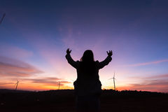 Silhouette tourist woman raised hand to sunset on the turbine at Royalty Free Stock Images