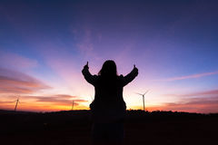 Silhouette tourist woman raised hand to sunset on the turbine at Royalty Free Stock Image