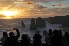 Silhouette of Tourists looking at the Twelve Apostles Great Ocean Road in Victoria Australia. Silhouette of unrecognizable tourists at Port Campbell National stock image