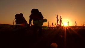 Silhouette of tourists rising on top of mountain. Silhouette of a couple of tourists with hiking backpacks ascending to the top of the mountain at sunset, slow stock video footage