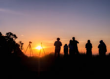 Silhouette tourists stand looking view at sunset Stock Photos