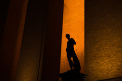 Statue Silhouette. Silhouette towards a yellow brick wall royalty free stock photo