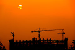 Silhouette of tower crane on construction site at sunset Stock Photo
