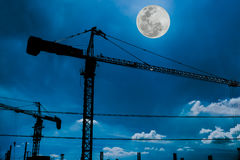 Silhouette of tower cranes on construction site with full moon a Stock Photography