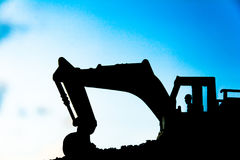 Silhouette tracked excavator Sand and stone And sky background Stock Images