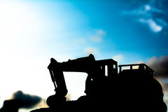 Silhouette tracked excavator Sand and stone And sky background Royalty Free Stock Photography