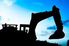 Silhouette tracked excavator Sand and stone And sky background Stock Photography