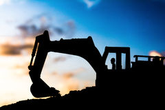 Silhouette tracked excavator Sand and stone And sky background Stock Photos
