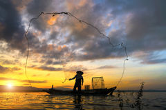 Silhouette of traditional fishermen throwing fishing net royalty free stock photo
