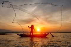 Silhouette of traditional fishermen throwing net fishing inle lake at sunrise time royalty free stock images
