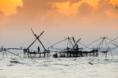 Silhouette of traditional fishing method using a bamboo square dip net with sunrise sky background Royalty Free Stock Photography