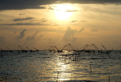 Silhouette of traditional fishing method using a bamboo square dip net with sunrise sky background Royalty Free Stock Photo
