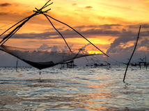 Silhouette of traditional fishing method using a bamboo square dip net with sunrise sky background Royalty Free Stock Images