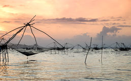 Silhouette of traditional fishing method using a bamboo square dip net with sunrise sky background Royalty Free Stock Image