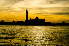 Silhouette of traditional pretty church complex on the canal in Venice, Italy royalty free stock photos