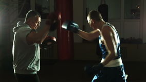 Silhouette of the trainer of the training young boxer on a ring stock video footage