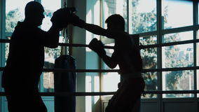Silhouette of the trainer of the training young boxer on a ring stock footage