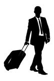 A silhouette of a traveler carrying a suitcase. A silhouette of a business traveler carrying a suitcase isolated on white background Royalty Free Stock Photography