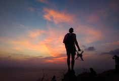 Silhouette of traveler controlling copter and photographing colorful sunrise. Man makes aerial photo and video of sunset sky on be stock image