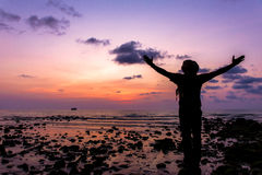 Silhouette of traveler with hands up in the sunset on the ocean Royalty Free Stock Photos