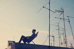 Silhouette of traveler sitting and resting on the chair on the roof in the city. Silhouette of young traveler sitting and resting on the chair on the roof in the Royalty Free Stock Photos