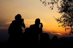 Silhouette of travelers with camera during sunset Royalty Free Stock Images