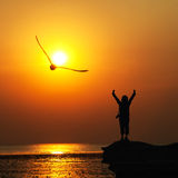 Silhouette of traveller with hands raised to birds flying in to Stock Images