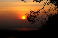 Silhouette of tree branches and leaves in autumn in front of the sun at sunset Stock Photography