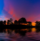 Silhouette of trees. With colourful sky and water reflections Stock Photos