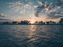 Silhouette of Trees Near Body of Water During Sunset Royalty Free Stock Photo