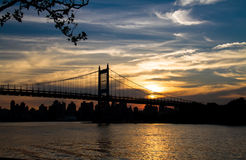 Silhouette of Triborough bridge over the river and city with sunset sky. New York Stock Images