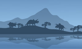 Silhouette of triceratops in the riverbank Royalty Free Stock Photo