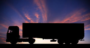 Silhouette of a truck on road at sunset Royalty Free Stock Photos