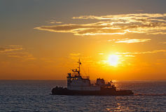 Silhouette of a tug boat at sunset Stock Image