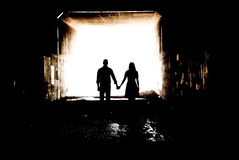 Silhouette in a Tunnel. Young couple holding hands in a tunnel Stock Photos