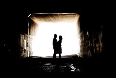 Silhouette in a Tunnel. Young couple holding hands in a tunnel Royalty Free Stock Photography
