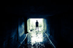 Silhouette in the tunnel. A man stands at the exit of the tunnel Royalty Free Stock Photo