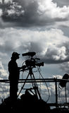 Silhouette of a TV cameraman against cloudy sky. Silhouette of a TV cameraman against a cloudy sky Stock Image
