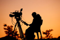 Silhouette of a TV cameraman. Against a sunset Royalty Free Stock Image