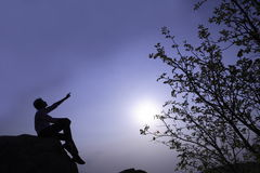 Silhouette at twilight. Silhouette of a person pointing upwards to the sky at twilight Stock Images