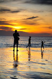 Silhouette of two adults and a child Stock Images