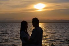 The silhouette of two adults for young couples embrace the waist together happy. With the beautiful sunset light stock photos