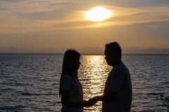 The silhouette of two adults for young couples embrace the waist together happy. With the beautiful sunset light stock image