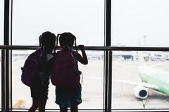 Silhouette of two asian child girls with backpack looking at plane and waiting for boarding in the airport. Together royalty free stock photo