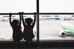 Silhouette of two asian child girls with backpack looking at plane and waiting for boarding in the airport. Together stock photo