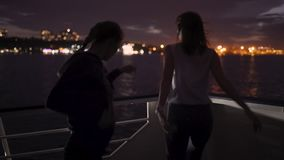 Silhouette of two beautiful young women dancing on ship deck at night. Girlfriends on the boat. Silhouette of two attractive young women traveling on a ship at stock video footage