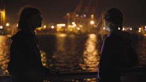 Silhouette of two attractive young women traveling on a ship at night. Girlfriends on the boat. In Odessa stock video